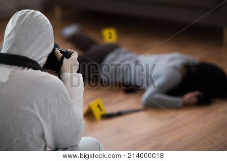 investigation, forensic examination and people concept - criminalist with camera photographing dead female victim body at crime scene