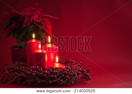 Red burning Advent Christmas candles with the berries wreath and poinsettia on a red background. Toned.