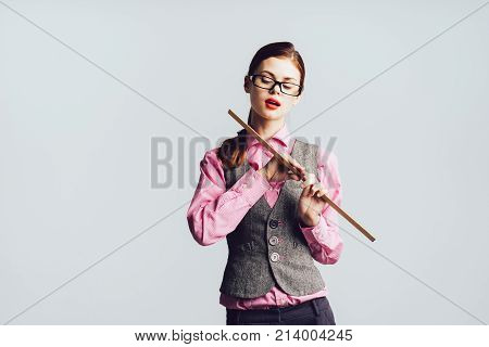 girl in glasses and in a pink shirt sexy looks down and holds a two-handed ruler, isolated