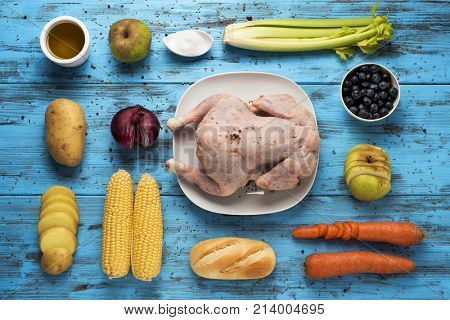 high-angle shot of a blue wooden table full of ingredients to prepare a stuffed turkey, such as a raw turkey, apple, onion, oil, blueberries or carrot, and other ingredients such as corns on the cob