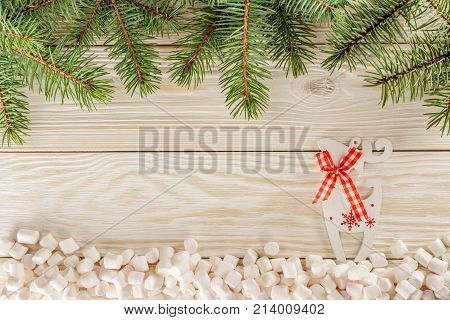 Christmas theme. Greeting card with place for Your text. White wooden background and marshmallows instead of snow. Reindeer Prancer.