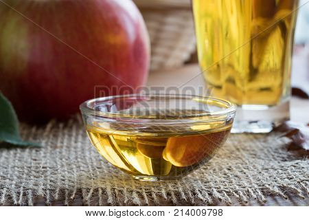 Apple cider vinegar in a glass bowl with an apple in the background