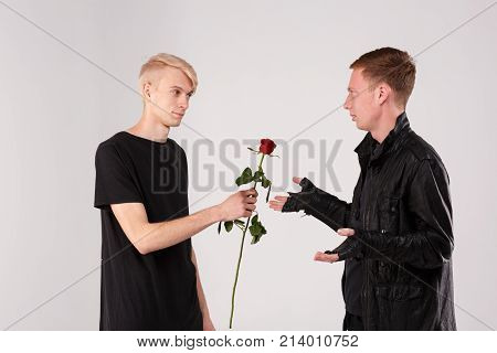 Two young guys are brunette and blond. A guy with blonde hair gives a brunette guy a rose to a who is indignant. Isolation.