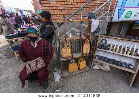 OLGIY, BAYAN-OLGIY, MONGOLIA - SEP 27, 2017: Unknown woman in the city market sells musical instruments and daggers. In Bayan-Olgiy province is populated to 88,7% by Kazakhs.