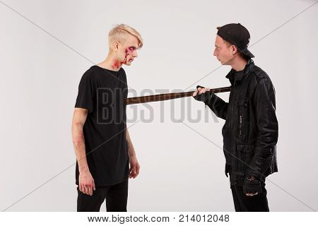 A dangerous guy in a cap and a wooden bit in his hands is threatening a battered boy. Isolation.