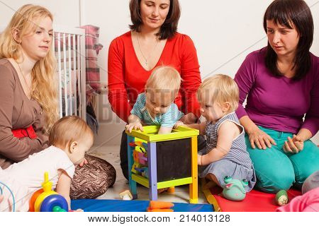 Group of mothers with their children gathered to talk and for communication between kids