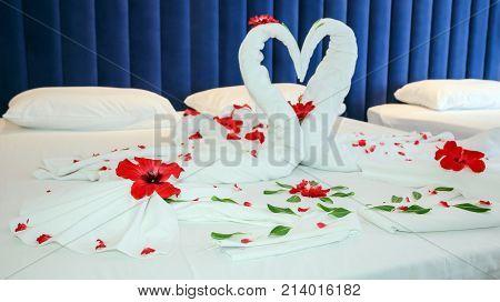 Romantic Flower Petal Arrangement On A Hotel Bed.  Towels Arranged As Swans In A Luxury Hotel.