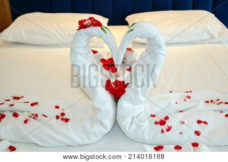 Towels Arranged As Swans In A Luxury Hotel. Bedroom In Hotel Suite With Heart Shaped Decorations. In