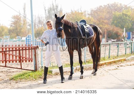 A young and attractive girl in riding equipment stands near a beautiful dark horse. Outdoors.