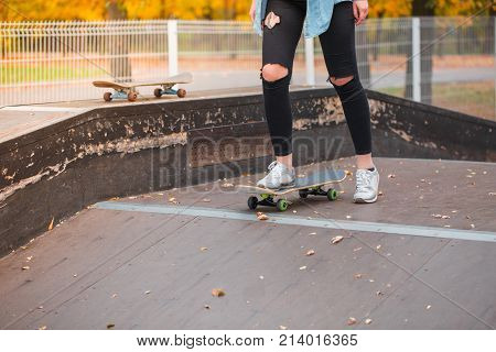 A girl in tattered pants on her knees is standing with one foot on a skateboard in a skate park