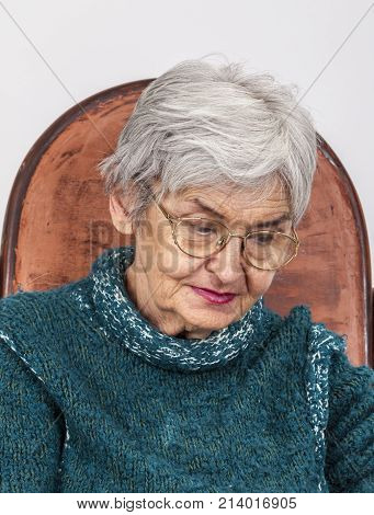 Portrait of a sad old woman with glasses.