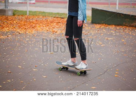 A girl in tattered pants is standing with her two feet on a skateboard in a skate park on the background of leaves