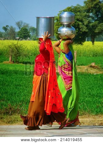 Agra, India-february 1: Unidentified Women Carry Water Jugs On Their Heads In The Countryside On Feb