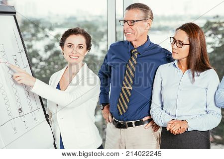 Happy businesswoman presenting bar chart on whiteboard to her concentrated colleagues at meeting in conference room