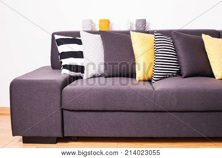 Gray sofa with many colorful pillows on it
