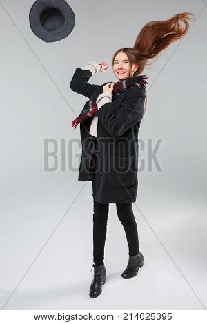 Beautiful brunette in a black coat on a gray background in the studio smiling, tossed the hat up, with the hair disbanded.