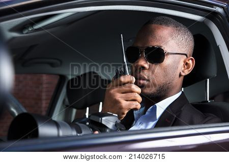 Private Detective Sitting Inside Car Holding SLR Camera And Walkie Talkie poster