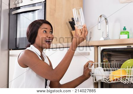 Happy African Woman Holding Drinking Glass From Dishwasher