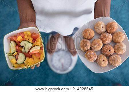 High Angle View Of A Person Standing On Weighing Scale Holding Fresh Fruits And Cookies