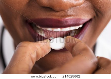 Close-up Of An African Woman Taking Medicine Pill