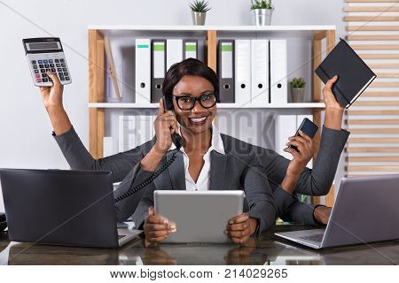 Tired Young African Woman Doing Multitasking Work On Laptop In Office