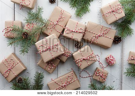 Christmas presents and gift boxes wrapped in kraft paper and fir tree decorations on white wooden background, copy space