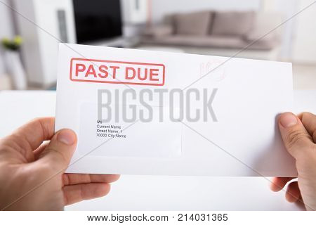 Close-up Of A Person's Hand Holding Past Due Bill Envelope