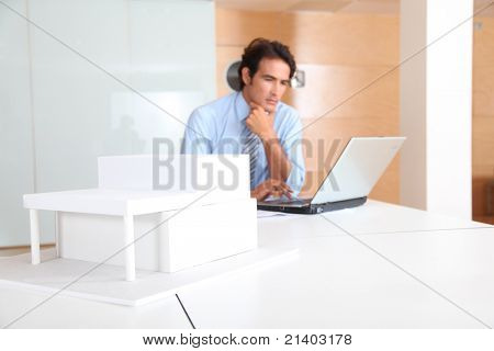 Architect in office with model of house in foreground