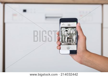 Close-up Of Woman's Hand Showing Dishwasher App On Mobile Phone In Kitchen