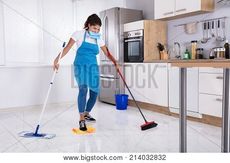 Young Female Janitor Multitasking By Sweeping And Mopping In Kitchen At Home
