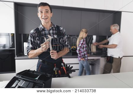 The plumber is posing in the kitchen. He holds a wrench in his hands and smiles. Behind him is a client and communicates with the second plumber. A black toolbox is next to it.