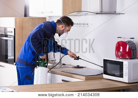 Pest Control Worker In Uniform Spraying Pesticide With Sprayer In Kitchen poster