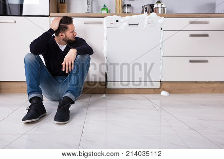 Upset Man Sitting Next To Dishwasher With Foam Coming Out In Kitchen