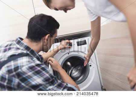 The woman called the repairman of the washing machine. She, along with the master, examines the washing machine. They are in the woman's bathroom.
