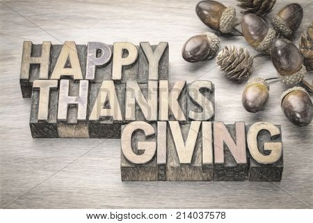 Happy Thanksgiving greeting card - word abstract in vintage letterpress wood type with acorns and cones fall decoration, digital charcoal painting effect