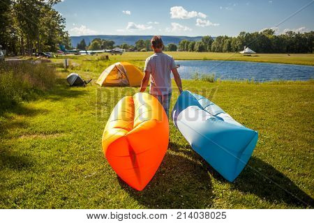 Man walking with Inflatable sofas out in the wild camping