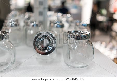 Glass jar with silver screw lid and closed up lid front view on white pattern mat against blurred background.