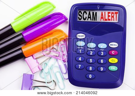 Scam Alert Text In The Office With Surroundings Such As Marker, Pen Writing On Calculator. Business
