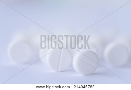 Soft focus white pills aspirin on white background. Medical and health care concept.