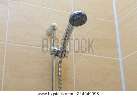 Eco-shower head with a metal shower hose against a light tile