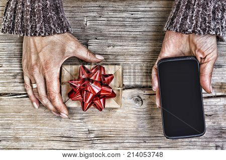 Closeup Of A Smartphone In The Hands Of A Woman And A Gift Box With A Red Bow On A Wooden Table. Fre