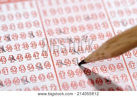 Close up of a lottery ticket and pen isolated on white background.