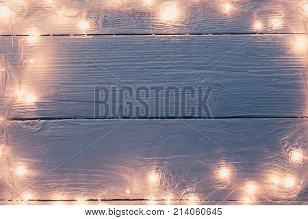 Picture of Christmas wooden gray table with burning garland on perimeter.