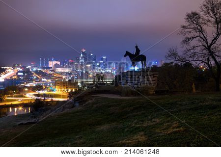 A skyline view of Kansas City Missouri during the twilight hours with overcast skies