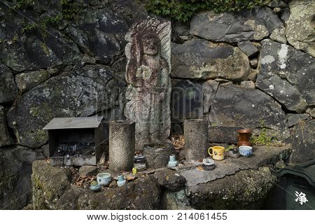 Nara, Japan -  May 31, 2017: Old stone sculpture honoured with cups of water and incense in the Kasugayama Primeval Forest