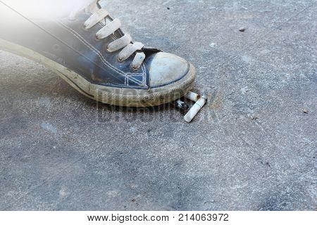 No Smoking Concept.the Old And Dirty Sport Shoe Treading The White Cigarette On Cement Ground