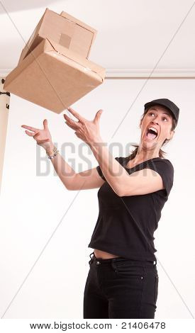 Stressed female courier trying to catch falling parcels