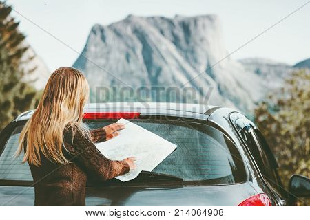 Woman car driver with map on road trip planning journey route in Norway Travel Lifestyle concept adventure vacations outdoor mountains on background