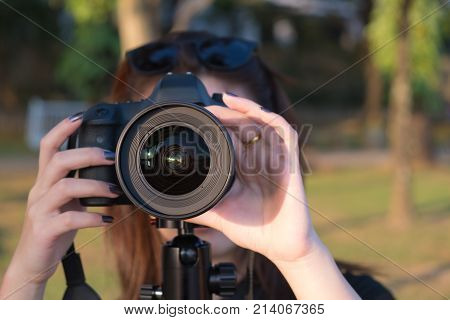 Professional photographer. Young woman checking focus before taking landscape photograph on tripod.