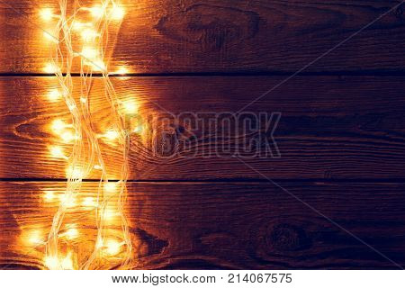 Photo of wooden surface with burning garland on side. Empty place for congratulations